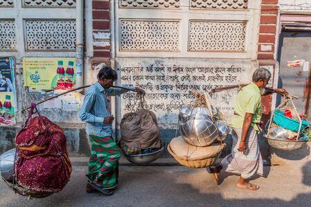 DHAKA, BANGLADESH - NOVEMBER 22, 2016: Local men carrying shoulder poles in Old Dhaka, Bangladesh