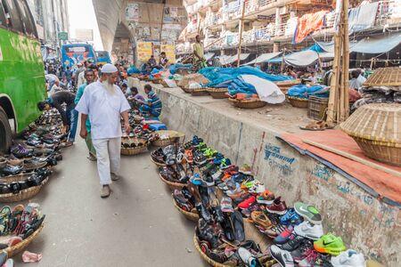 DHAKA, BANGLADESH - NOVEMBER 21, 2016: Shoe sellers with their merchandise on a street in Dhaka, Bangladesh