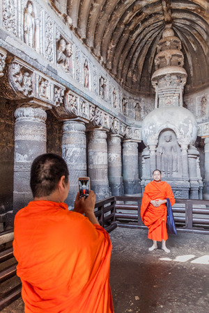 AJANTA, INDIA - FEBRUARY 6, 2017: Buddhist monks taking photos in the chaitya (prayer hall), cave 19, carved into a cliff in Ajanta, Maharasthra state, India
