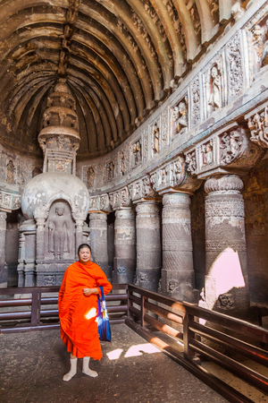AJANTA, INDIA - FEBRUARY 6, 2017: Buddhist monk in the chaitya (prayer hall), cave 19, carved into a cliff in Ajanta, Maharasthra state, India