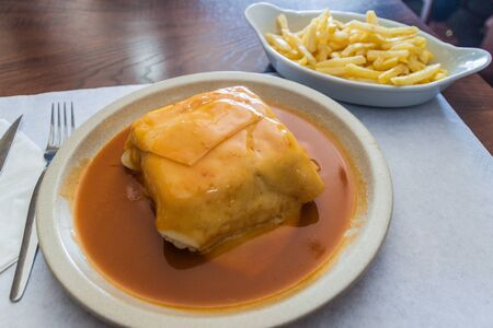 Sandwich called Francesinha served with french fries, typical dish in Porto, Portugal Imagens