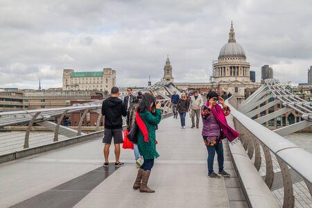 LONDON, UNITED KINGDOM - OCTOBER 4, 2017: People are crossing the Millenium Bridge in London. Stock Photo