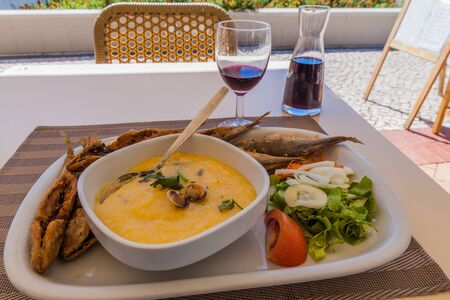 Food in Faro, Portugal. Xarem (mash made of corn flour with clams) with fried fish, salad and wine.