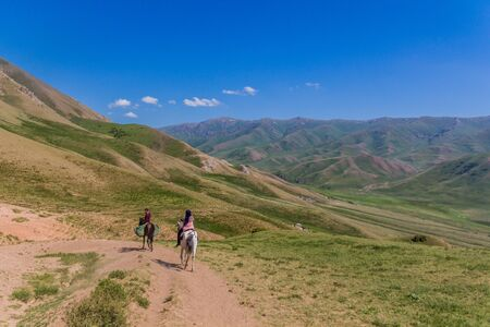 Horse riders in mountains near Song Kul lake, Kyrgyzstan