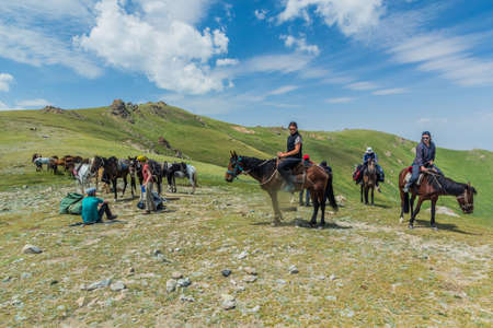 SONG KUL, KYRGYZSTAN - JULY 23, 2018: Tourists ride horses near Song Kul lake, Kyrgyzstan Éditoriale