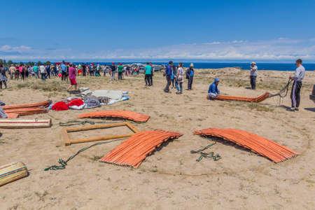 ISSYK KUL, KYRGYZSTAN - JULY 15, 2018: Local people building a yurt at the Ethnofestival Teskey Jeek at the coast of Issyk Kul lake in Kyrgyzstan Editöryel
