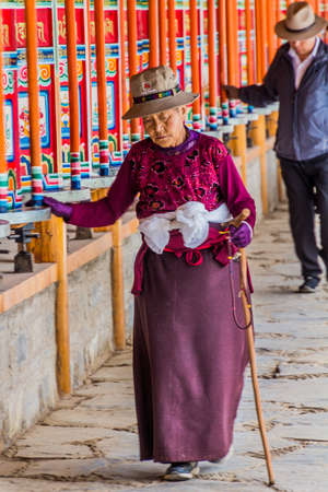 XIAHE, CHINA - AUGUST 25, 2018: Devotees pass a row of praying wheels around Labrang Monastery in Xiahe town, Gansu province, China