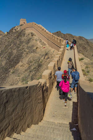 JIAYUGUAN, CHINA - AUGUST 22, 2018: Tourists visit Overhanging Great Wall near Jiayuguan, Gansu Province, China