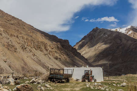 Village house and tractor in Gunt river valley in Pamir mountains, Tajikistan