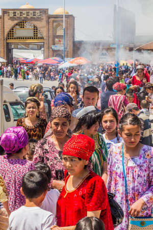 PENJIKENT, TAJIKISTAN - MAY 9, 2018: People on a street in front of bazaar in Penjikent, Tajikistan