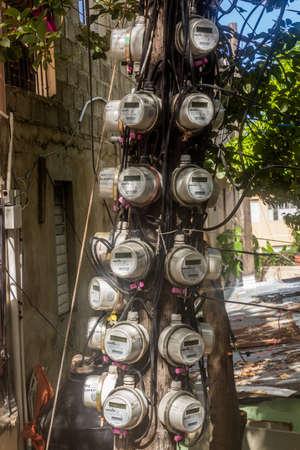 PUERTO PLATA, DOMINICAN REPUBLIC - DECEMBER 15, 2018: Various electricity meters on a pole in Puerto Plata, Dominican Republic Editorial