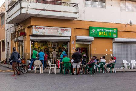 SANTO DOMINGO, DOMINICAN REPUBLIC - DECEMBER 2, 2018: Local people gathered at a colmado (corner shop) in Santo Domingo, capital of Dominican Republic. Editorial