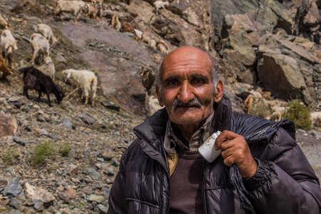 BARTANG, TAJIKISTAN - MAY 20, 2018: Sheep and goat herder in Bartang valley in Pamir mountains, Tajikistan