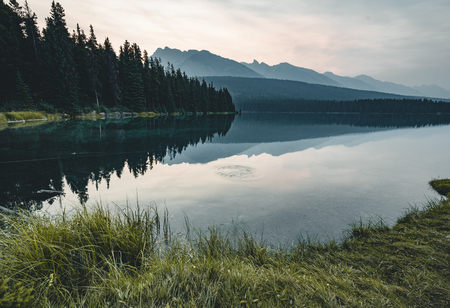 Sunrise and misty morning over Mount Rundle at Two Jack Lake in Stock Photo