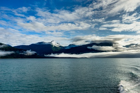 Mountains covered in clouds on a misty morning on the Ferry towa Stock Photo