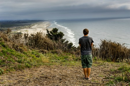 Young man overlooking beach Coastel View with Pacific Ocean