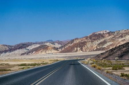 Empty street and blue sky in Death Valley National Park California Stock Photo