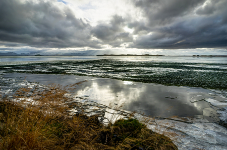 Winter Landscape frozen lake with ice floes and cloudy sky in Ic