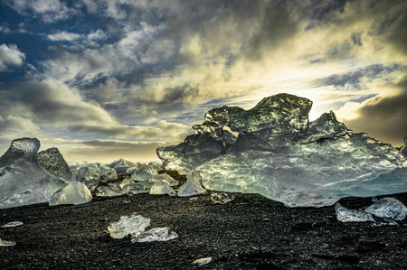 Icebergs floating in Jokulsarlon at sunset golden hour with glac Stock Photo
