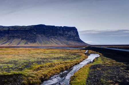 Icelandic Landscape with mountains and river with grass and stre