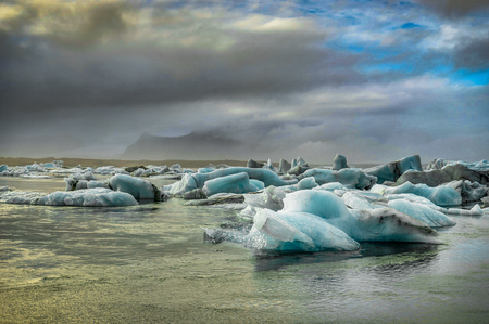 Icebergs floating in Jokulsarlon at sunset golden hour with glac Banco de Imagens