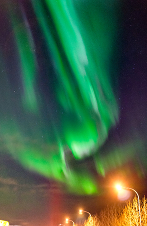 Northern lights Aurora Borealis above street in Iceland Stock Photo