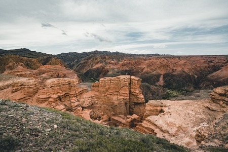 Charyn Grand Canyon with clouds and sun red orange stone Martian landscape