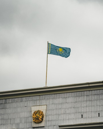 Flag of Kazakhstan on a cludy day on top of a building