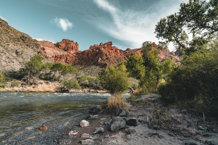 Grand Canyon Charyn River with trees blue sky red stone