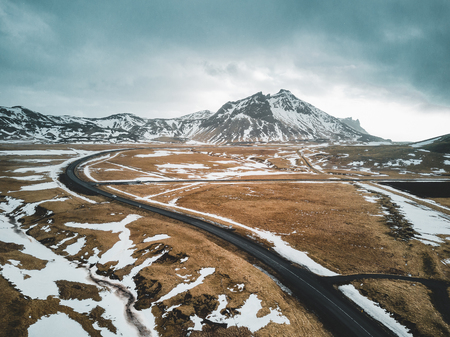 Iceland aerial view Landscape with snow and clouds, street and yellow and green grass