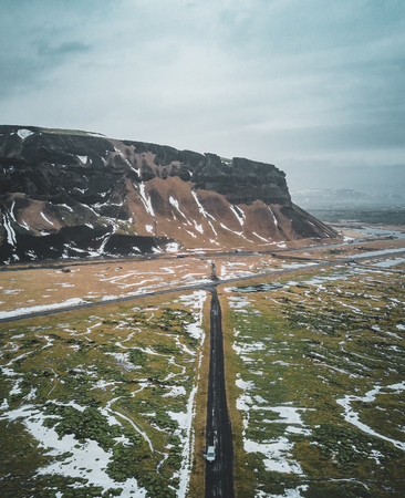 Aerial photograph of mountain and ringroad in iceland with green moss and snow