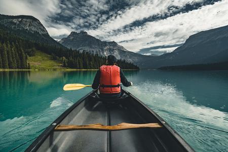 Hombre joven en canoa en el lago Esmeralda en las montañas rocosas de Canadá con canoa y chaleco salvavidas con montañas en el agua azul de fondo. Foto de archivo