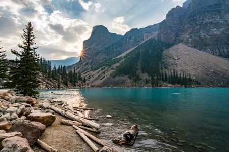 Sunrise with turquoise waters of the Moraine lake with sin lit rocky mountains in Banff National Park of Canada in Valley of the ten peaks. Stock Photo