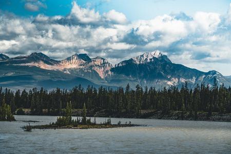El río Athabasca fluye por las montañas rocosas canadienses en Alberta, Canadá Foto de archivo