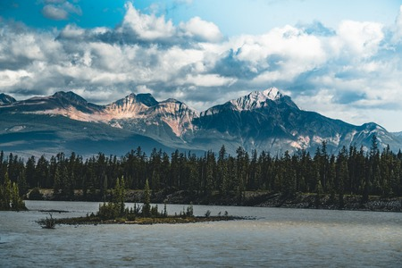 the Athabasca river flows by the Canadian rocky mountains in Alberta, Canada 版權商用圖片 - 105134736