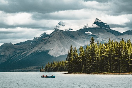 a canoe on maligne lake in summer with a backdrop of the canadian rockies in jasper national park, alberta, canada Фото со стока