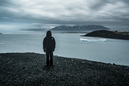Young man overlooking jokursarlon glacial lagoon on a misty day in south Iceland Stock Photo