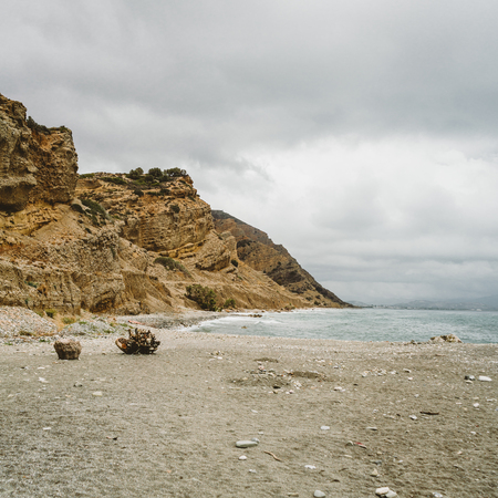Typical beach scene in island crete. View towards ocean. With Mountains in background on a cloudy day.