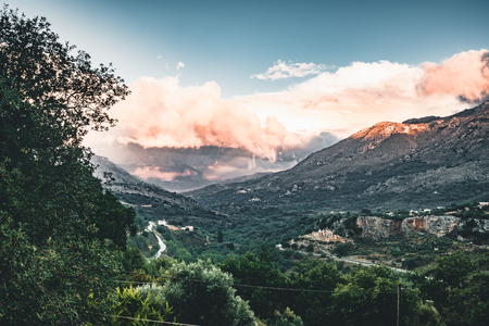 Sunset View on mountains with low hanging clouds orange twilight and green trees. South Crete neat Rethymno, Greece