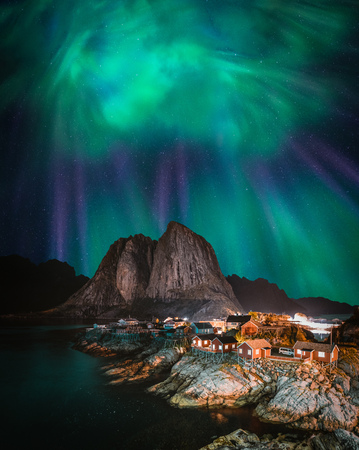 Northern Lights Aurora Borealis with classic view of the fisherman s village of Hamnoy, near Reine in Norway, Lofoten islands. This shot is powered by a wonderful Northern Lights show. Фото со стока