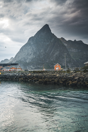 Yellow rorbu houses of Sakrisoy fishing village on a cloudy day with mountains in the background. Lofoten islands, Norway Stock Photo