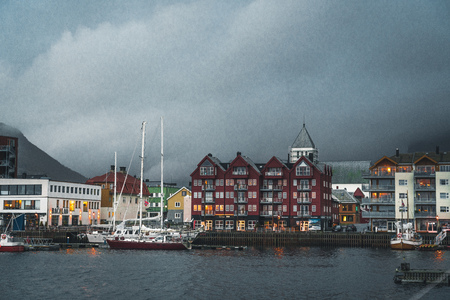 Svolvaer, Norway - September 2018: Boats in the waterfront harbor with mountains in the background. Svolvaer is a fishing village and tourist town located on Austvagoya in the Lofoten Islands.