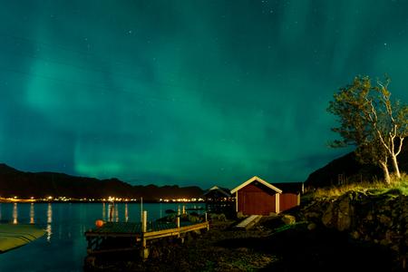 Northern lights Aurora Borealis over illuminated fishing village of reine lofoten islands.