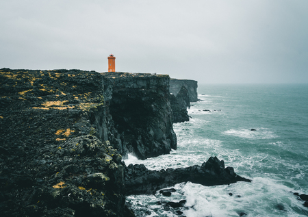 Orange Lighthouse Svortuloft Skalasnagi tower in Snaefellsnes Peninsula, west Iceland on an overcast day.