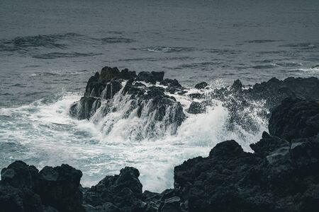 Azores, Big waves crashing over black volcanic rock on the Atlantic Ocean in the coast of Sao Miguel island in the Azores, Portugal Imagens - 127424569