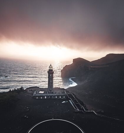 View over Capelinhos volcano, lighthouse of Ponta dos Capelinhos on western coast on Faial island, Azores, Portugal with a dramatic sunset and strong waves and clouds. Last volcano eruption was in 1957.
