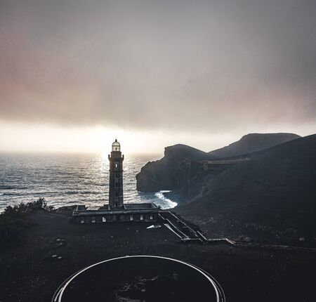 View over Capelinhos volcano, lighthouse of Ponta dos Capelinhos on western coast on Faial island, Azores, Portugal with a dramatic sunset and strong waves and clouds. Last volcano eruption was in 1957. Imagens - 127424578