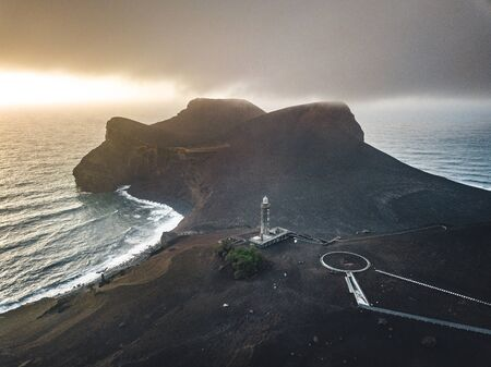 View over Capelinhos volcano, lighthouse of Ponta dos Capelinhos on western coast on Faial island, Azores, Portugal with a dramatic sunset and strong waves and clouds. Last volcano eruption was in 1957. Imagens - 127424634