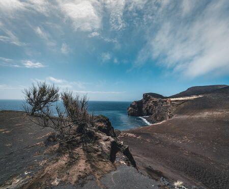 View over Capelinhos volcano, lighthouse of Ponta dos Capelinhos on western coast on Faial island, Azores, Portugal on a sunny day with blue sky and clouds and waves. Last volcano eruption was in 1957. Imagens - 127424643