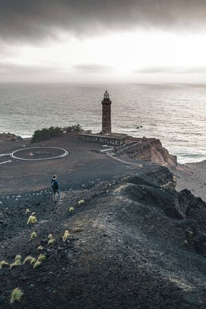 View over Capelinhos volcano, lighthouse of Ponta dos Capelinhos on western coast on Faial island, Azores, Portugal with a dramatic sunset and strong waves and clouds. Last volcano eruption was in 1957. Imagens - 127424689